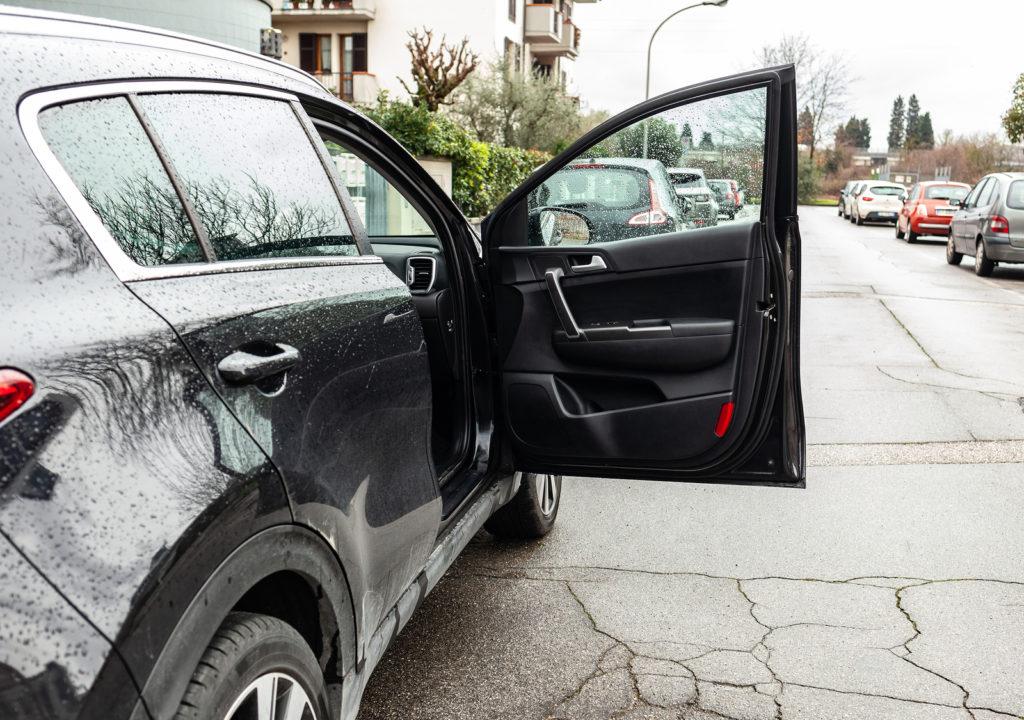 Verkehrsunfall: Kollision beim Öffnen einer Fahrzeugtür auf einem öffentlichen Parkplatz